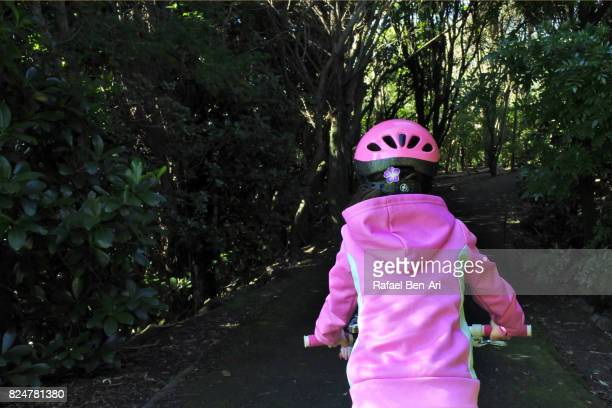 Young girl rides on a bike in a park