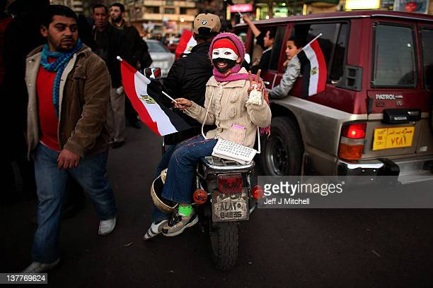 A young girl rides on the back of a motorcycle through Tahrir Square on January 26 2012 in Cairo Egypt Tens of thousands of Egyptian people gathered...