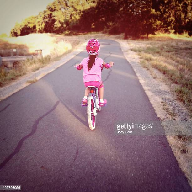 Young girl riding her bike on bike trail