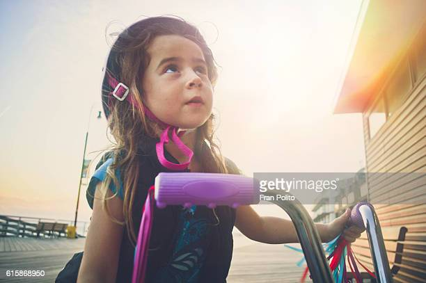 Young girl riding her bike on the boardwalk at the beach.