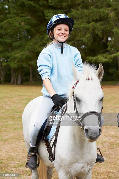 Young girl riding pony