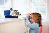 Young Girl Risking Accident With Pan In Brightly Lit Kitchen