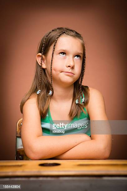 Young Girl Rolling Her Eyes, While Sitting at School Desk