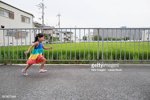 A young girl running along a footpath.