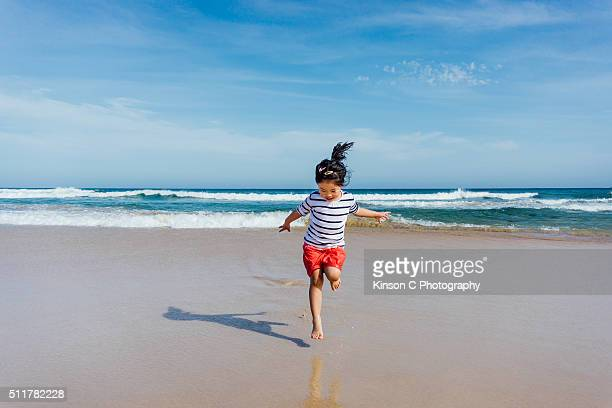 Young Girl Running And Jumping At Beach