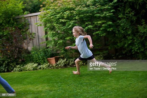 Young girl running in a backyard