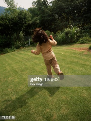 Young girl running in garden, rear view : Stock Photo
