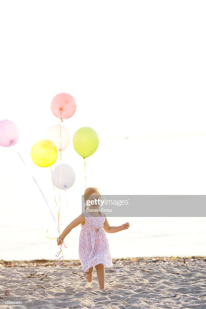 Young girl running on the beach with balloons : Stock Photo