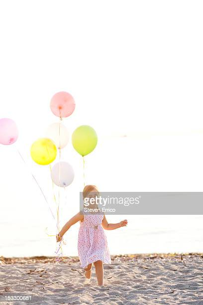 Young girl running on the beach with balloons