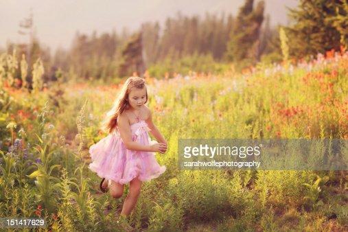 Young girl running through a field : Foto de stock