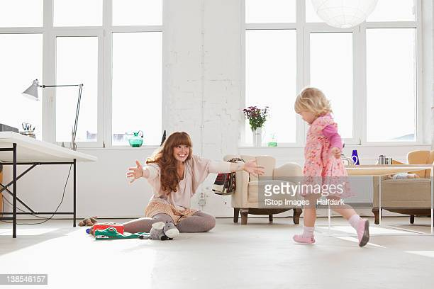 A young girl running towards her mother sitting on the floor