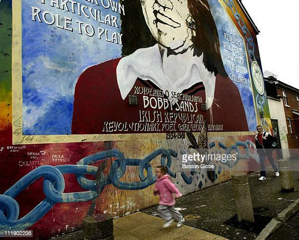 A young girl runs past a mural of Bobby Sands one of the most recognized murals on the Falls road area