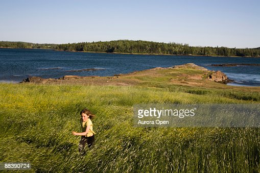 A young girl runs through a field at sunset with the inlets of coastal Maine in the background. : Stock Photo