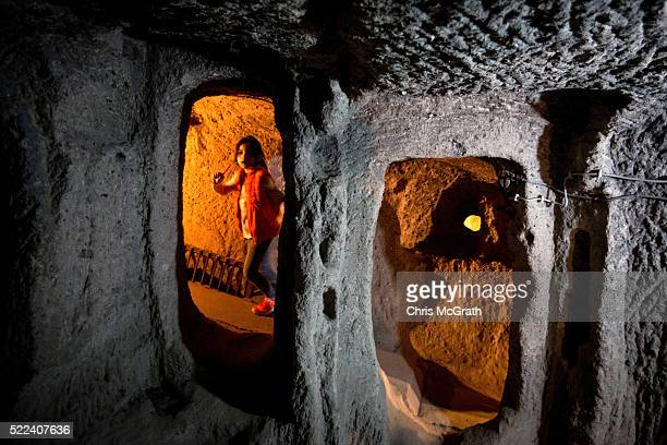 A young girl runs through a section of an underground city on April 17 2016 in Nevsehir Turkey Cappadocia a historical region in Central Anatolia...