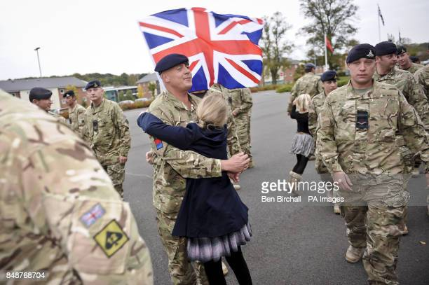 A young girl rushes forward with a Union Flag as soldiers from 19th Regiment Royal Artillery fallout on the parade square and are reunited with their...