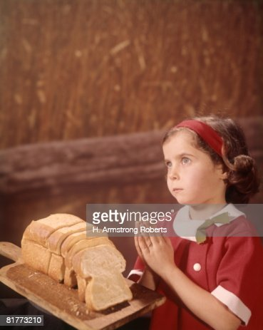 Young Girl Saying Prayer Praying Loaf Bread Wheat Field Background. : Stock Photo