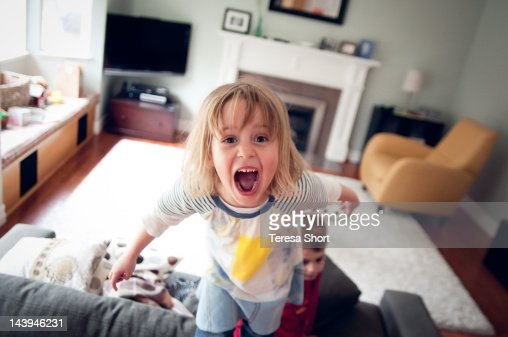Young girl screaming and standing on couch : Stock Photo