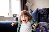 A young girl screaming at the camera in the house.