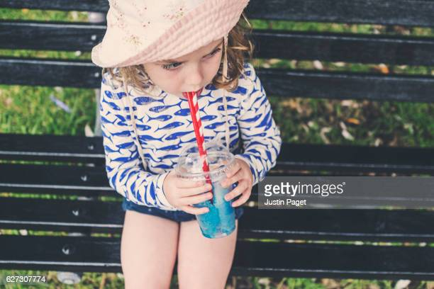 Young Girl seated on park bench drinking through Straw