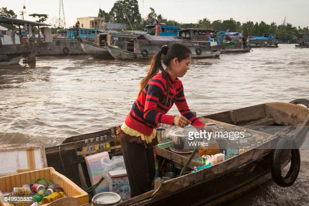 Young girl selling drinks from a boat in the floating market Cai Rang near Can Tho Mekong River Delta Vietnam