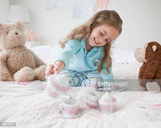 Young girl serving tea at tea party