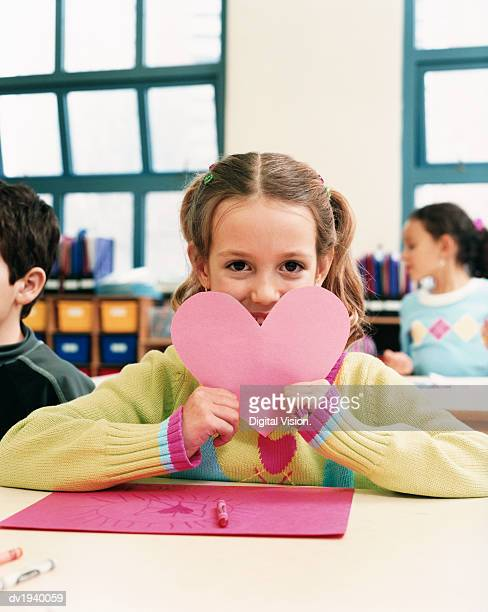 Young Girl Showing a Valentines Card She Made in Classroom