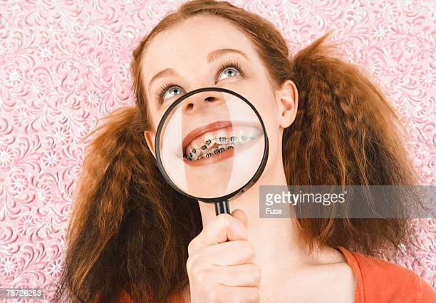 Young Girl Showing Her Braces with a Magnifying Glass