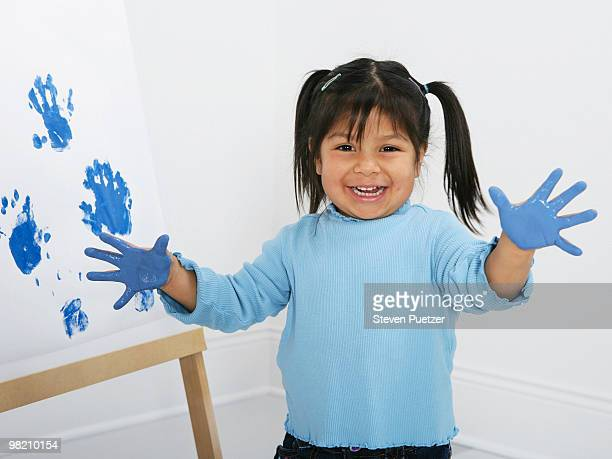 Young girl showing painted hands with handprints