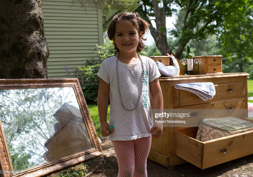 A young girl shows off her new necklace as buyers walk through a tag sale July 20, 2013 in Dorset, Vermont.