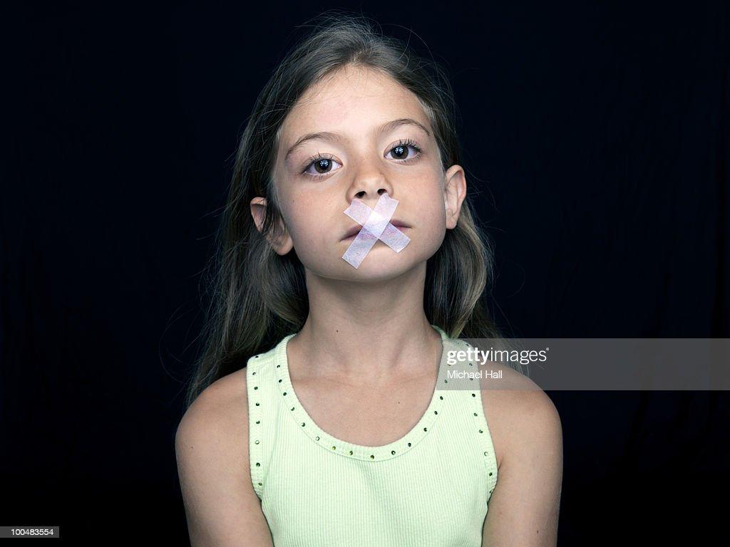 Young girl silenced : Stock Photo
