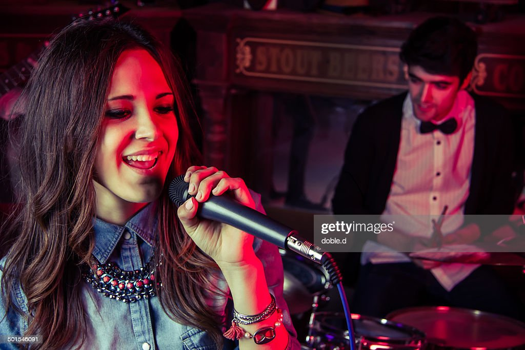 Young girl singer and her indie band in a club