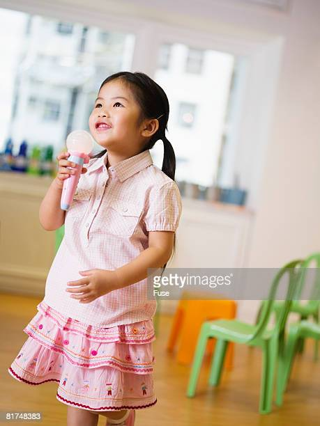 Young Girl Singing into Toy Microphone