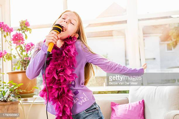 Young girl singing kareoke at home.