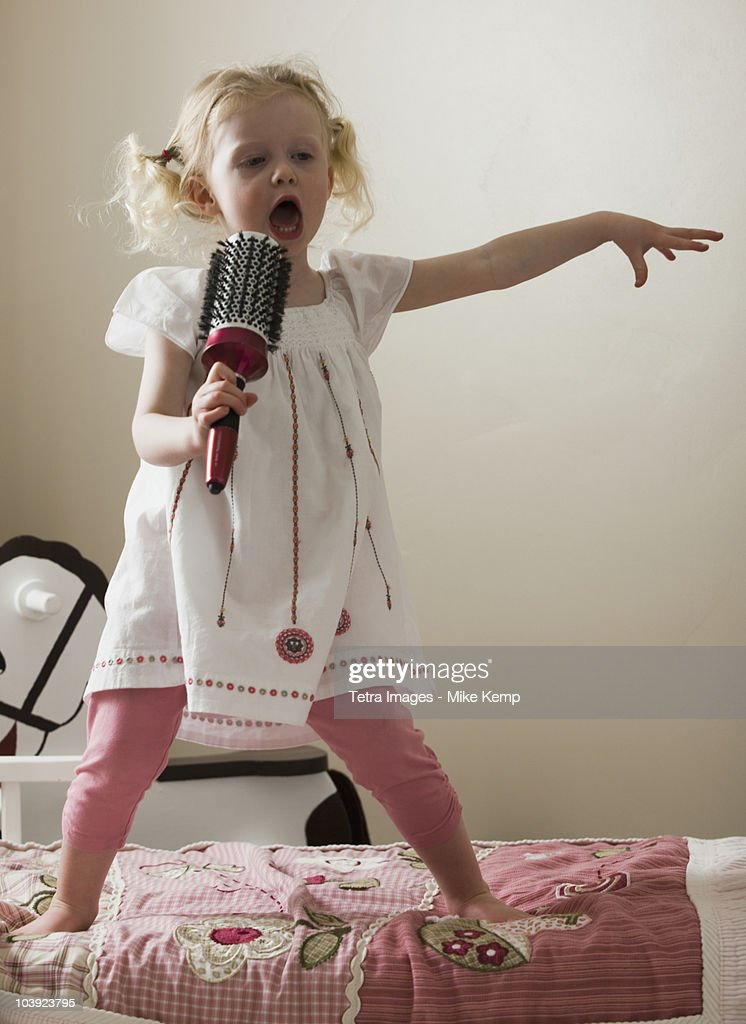 Young girl singing on her bed