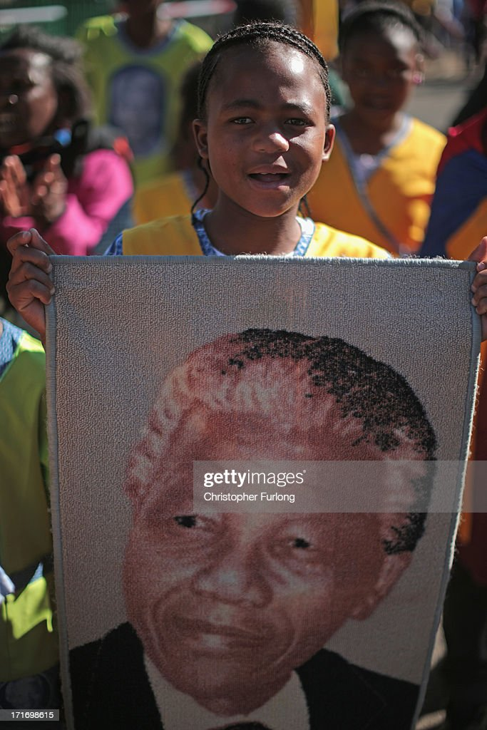 A young girl sings in honour of Nelson Mandela outside the Mediclinic Heart Hospital where he is being treated on June 28, 2013 in Pretoria, South Africa. People to continue to gather and lay flowers and tributes outside the Mediclinic Heart Hospital where Mandela is being treated for a lung infection on his 21st day in hospital.
