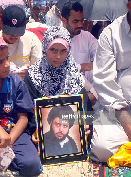A young girl sits among worshippers waiting to hear the weekly sermon holding a picture of firebrand cleric Muqtada al Sadr Friday July 18 2008...