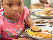 Young Girl Sits at a Table With a Plate of Fried Food for Breakfast, Looking Displeased