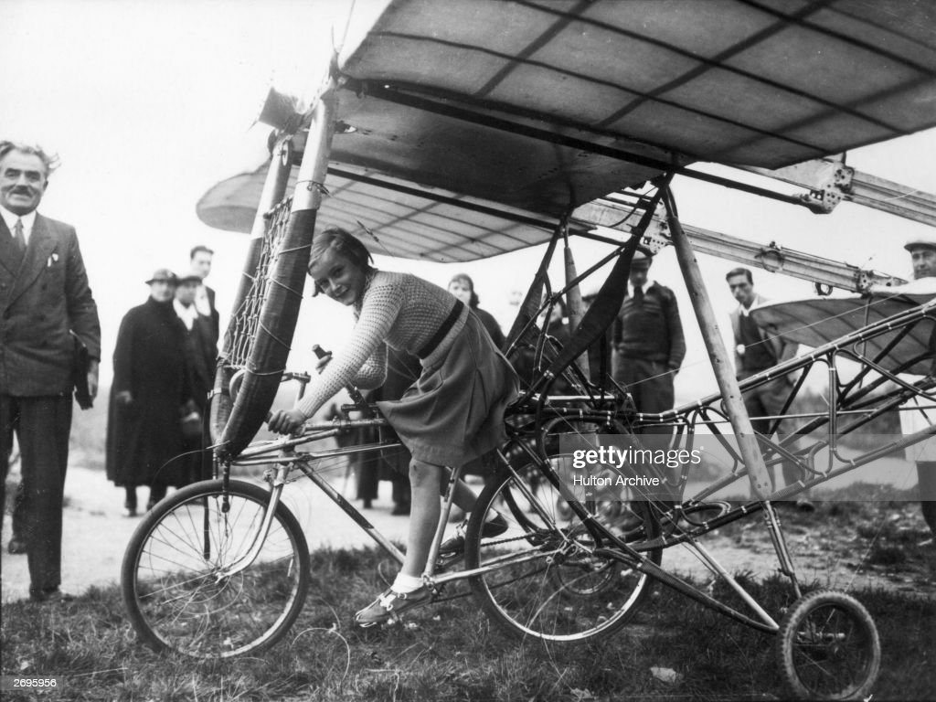 A young girl sits atop an aviation machine invented by Francois Baudot (standing, left), France. The machine was intended to fly after the bicycle reached a speed of thirty-five miles per hour.