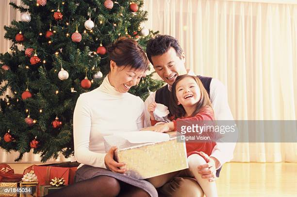 Young Girl Sits by a Christmas Tree With Her Parents, Smiling With Joy as She Opens a Christmas Present