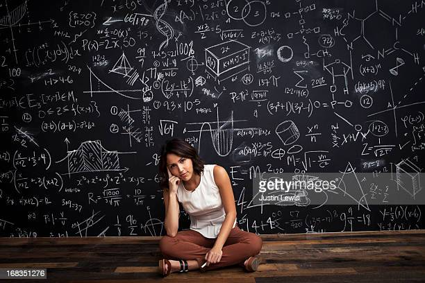 Young girl sits by mathematical chalkboarda