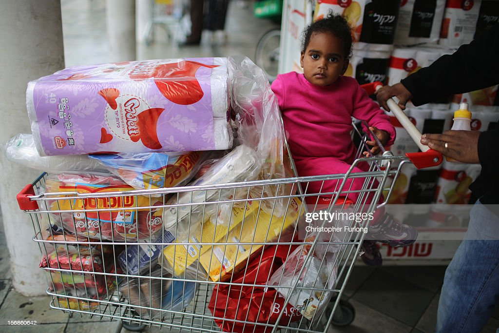 A young girl sits in a shopping trolley as families stock up with provisions as businesses get back to normal in the Israeli border town of Sderot on November 23, 2012 in Sderot, Israel. Daily life in the southern border towns of Israel are returning to normal after eight days of rockets and alerts during the recent conflict between Israel and Hamas militants in the Gaza Strip.