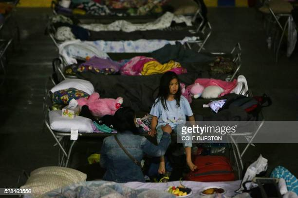 A young girl sits on a cot at a makeshift evacuee center in Lac la Biche Alberta on May 5 after fleeing forest fires north of Fort McMurray Raging...