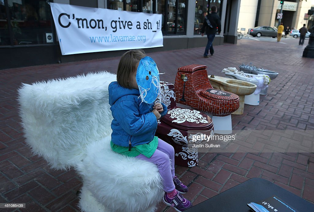 A young girl sits on a decorated toilet that is part of a public art installation titled 'C'mon, give a shit' to mark World Toilet Day and to bring attention to a project to convert retired MUNI buses into mobile showers for the homeless on November 21, 2013 in San Francisco, California. Lava Mae founder Doniece Sandoval coordinated the public art installation of decorated toilets to raise awareness about the millions of people around the world who do not have access to clean and private toilets. The installation also promotes the nonprofit Lava Mae's project to convert old San Francisco municipal buses into mobile showers for homeless people in the city.