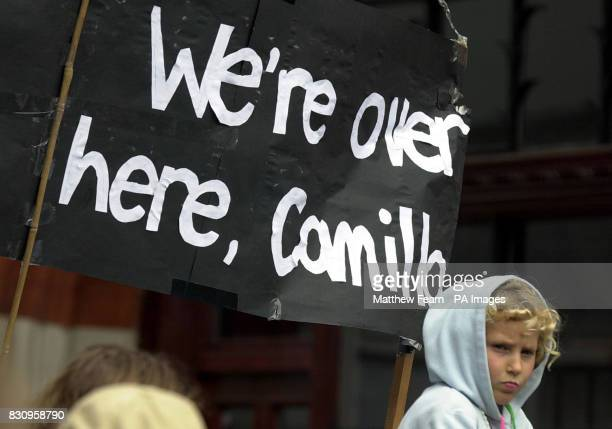 A young girl sits on an adult's shoulders in front of a banner proclaiming 'We're over here Camilla' on St James's Street in London during the...