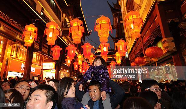 A young girl sits on her father's shoulders as they visit Yuyuan Gardens for the Lantern Festival in Shanghai on February 24 2013 China celebrates...