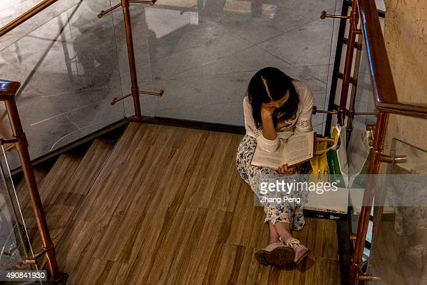 A young girl sits on stairs reading books in Fangsuo Book Store an independent book store opened in 2015 at the underground level of the Tai Koo Li...
