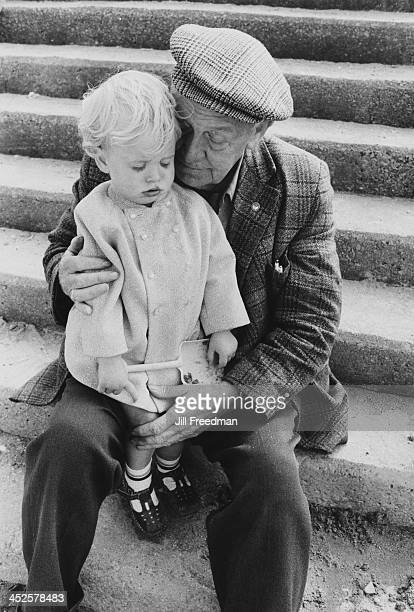 A young girl sits on the knee of an elderly man in Llandudno Wales 1974