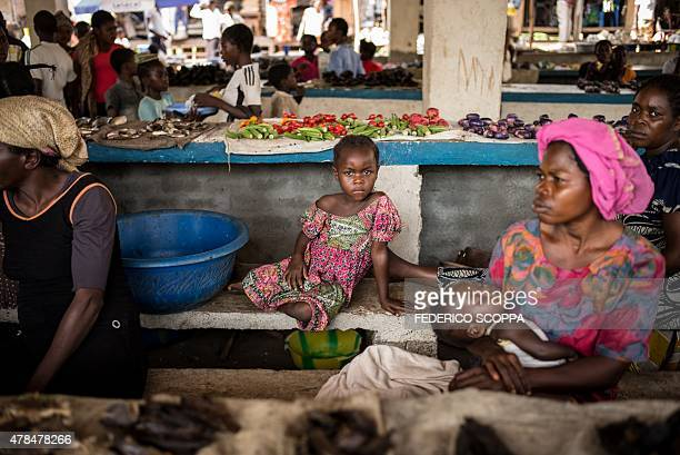 A young girl sitt on a bench at a market in Dongo north western region of Democratic Republic of Congo on June 24 2015 AFP PHOTO/FEDERICO SCOPPA