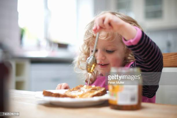 Young girl sitting at kitchen table, drizzling honey on toast