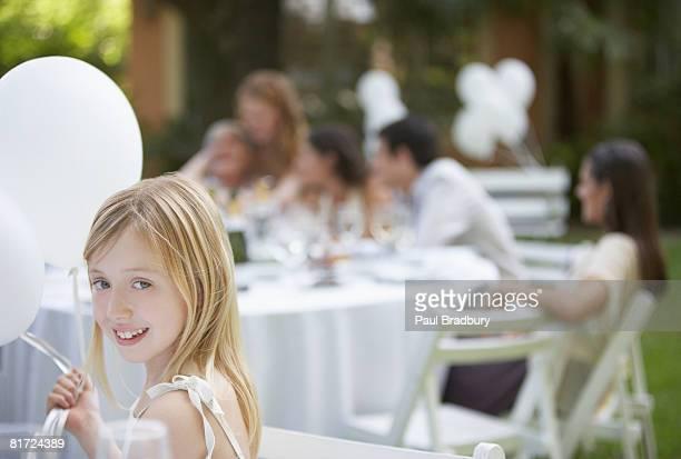 Jovem sentado ao ar livre com balões e sorridente Festa